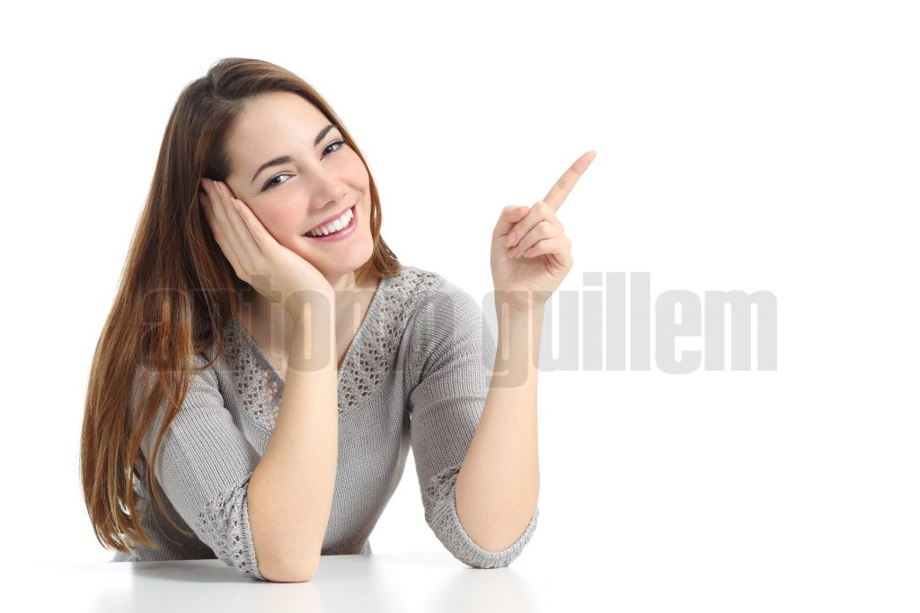 Happy woman pointing and presenting at side looking at camera isolated on a white background