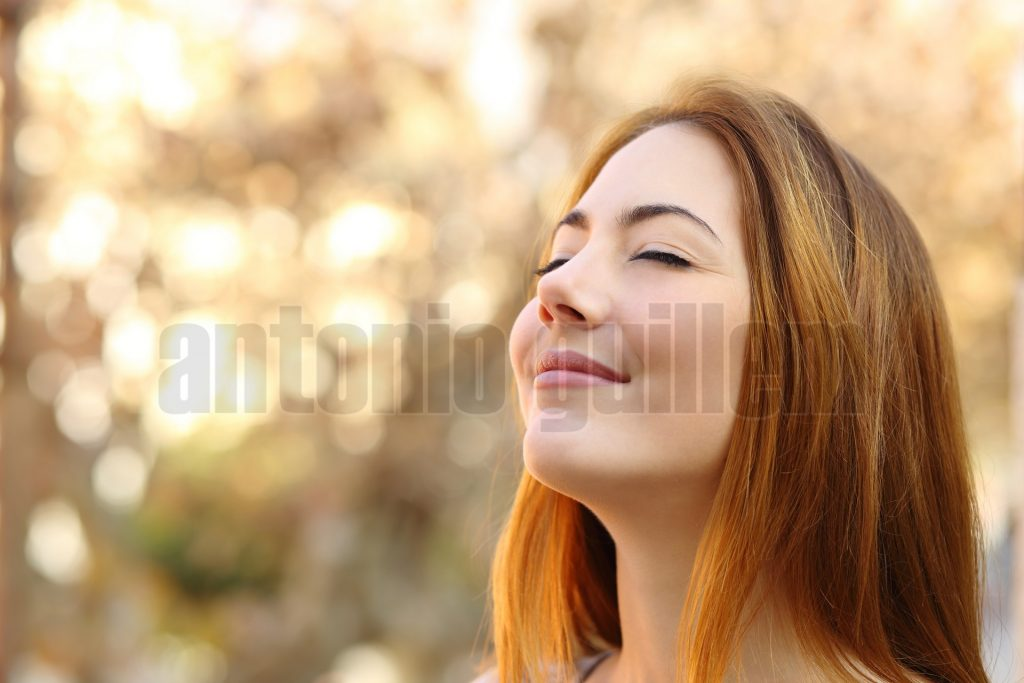 Portrait of a beautiful woman doing breath exercises with an autumn unfocused background