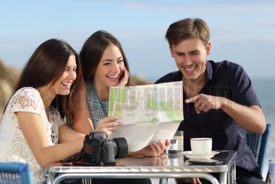 Group of young tourist friends consulting a paper map in a restaurant with the beach in the background