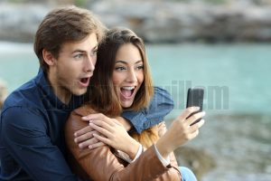 Shocked couple watching a smart phone on holidays on the beach