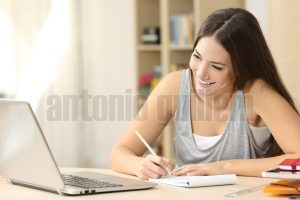 Happy student learning on line and taking notes in a notepad doing homework looking at laptop screen in a desk at home