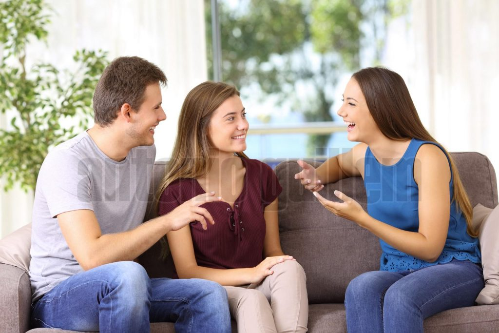 Three joyful friends talking on a couch at home