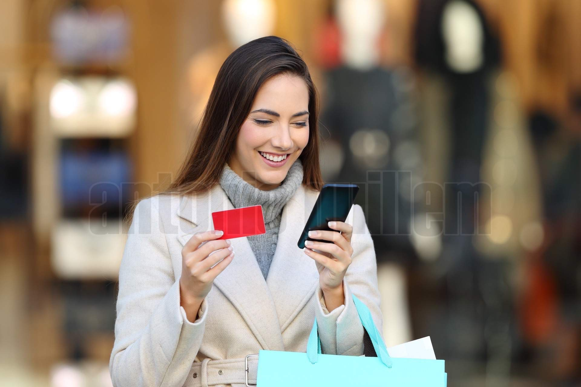 Shopper holding shopping bags paying on line