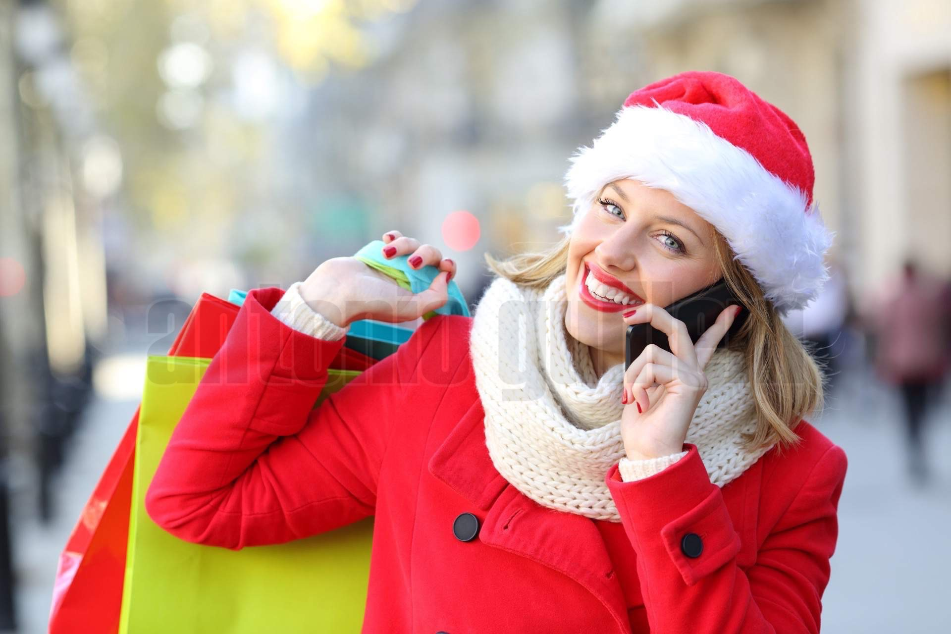 Happy shopper with shopping bags calling on phone in christmas