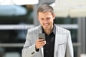Businessman walking and texting on phone (2)