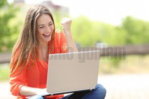 Euphoric woman searching job with a laptop in a park