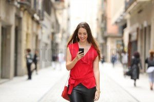 Fashion woman walking and using a smart phone (3)