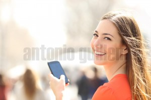 Happy woman walking in the street using a smartphone (1)