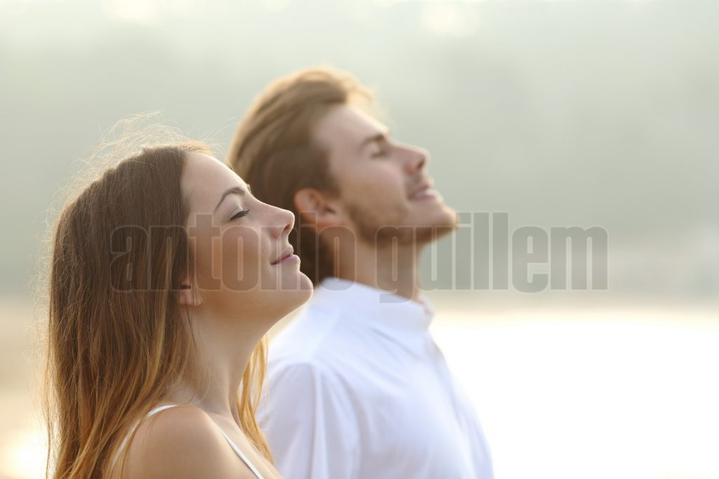Profile of a couple of man and woman breathing deep fresh air together at sunset