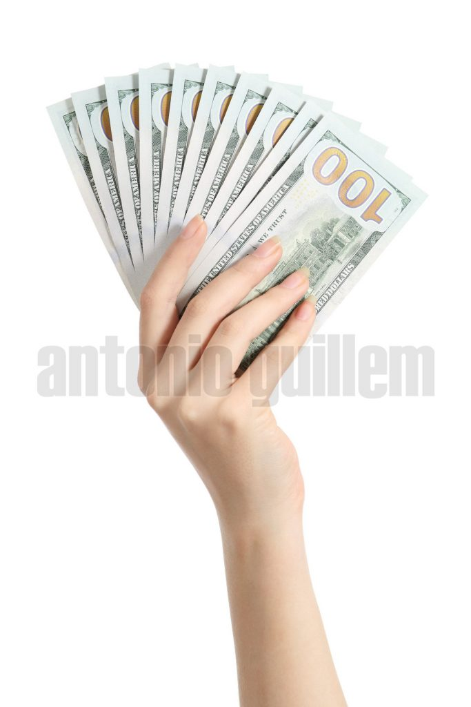 Hand holding money one hundred dollars banknotes isolated on a white background