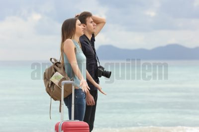 Tourists frustrated with the bad weather when arrive to the beach with the cloudy sky in the background