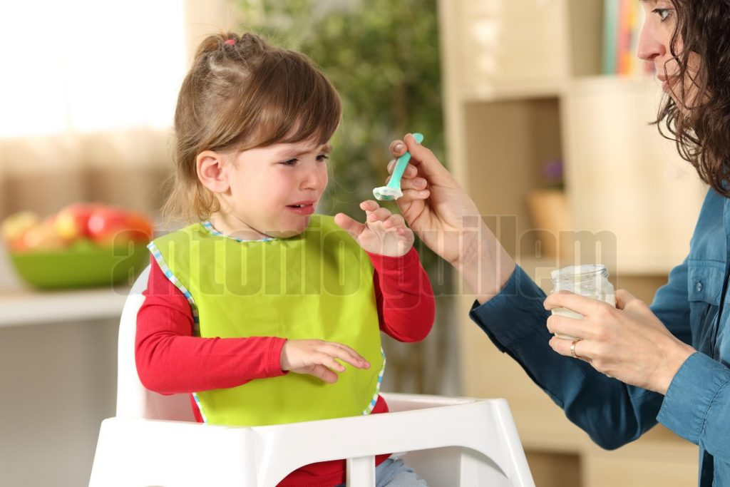 Toddler crying at lunch time sitting in a highchair in the living room at home with a homey background